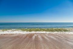 Een golf die zich op een zandig strand in Florida terugtrekken Stock Foto's