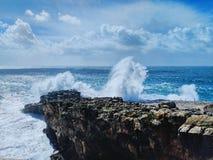 Een golf verplettert in de rotsen stock afbeeldingen