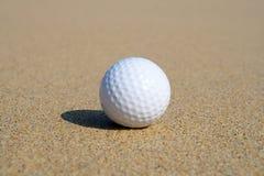 Een golfbal in het zand. stock fotografie