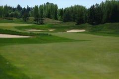 Een golfcursus met wegen, bunkers en vijvers en met het water geven stock fotografie