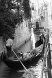 Een gondelier aandachtig bij het roeien op zijn gondel in een kanaal in Venetië royalty-vrije stock afbeelding
