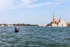 Een gondelier en San Giorgio Maggiore in Venetië, Italië stock foto's