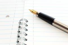 Een goud nibbed pen op een blocnote Royalty-vrije Stock Foto