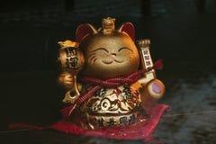 Een gouden Chinese gelukkige kat met zijn linkerdiepoot, op een rustieke houten oppervlakte wordt opgeheven stock fotografie