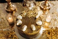 Een gouden verjaardagscake is verfraaid met macaroni royalty-vrije stock fotografie