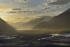 Een gouden zonsondergang in een brede bergvallei, tegen een achtergrond van donkere silhouetten van hoge heuvels die betrekt op d Royalty-vrije Stock Afbeeldingen