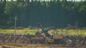 Een graafwerktuig laadt aarde in de stortplaatsvrachtwagen van de zandmijnbouw stock videobeelden