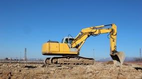 Een graafwerktuigniveaus de grond in het openen van een nieuwe industriële ontwikkelingsplaats stock foto