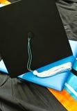 Een graduatie plaatste met GLB, leeswijzer, toga, kap en diploma. Stock Afbeelding
