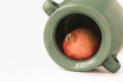 Een granaatappel binnen de groenachtige aarden kruik stock foto's