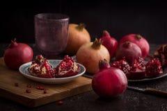 Een granaatappelstilleven met verse granaatappelvruchten en zaden op rustieke achtergrond Het bekijken Camera royalty-vrije stock fotografie