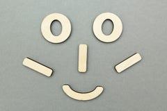 Een grappig houten gezicht op een grijze achtergrond stock afbeelding
