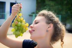 Een grappig meisje houdt in haar hand een grote bos van druiven stock foto's