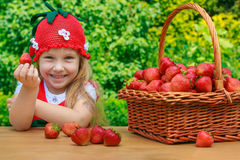 Een grappig meisje 4 jaar oud met een mand van aardbeien Stock Afbeeldingen