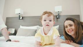 Een grappig meisje probeert om op het bed te kruipen en kijkt rond stock footage