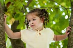 Een grappig vier-jaar-oud meisje met donkere ogen en een vlechtkapsel Royalty-vrije Stock Afbeeldingen