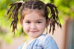 Een grappig vier-jaar-oud meisje met een kapsel in de vorm van vlechten Stock Afbeeldingen