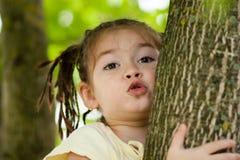 Een grappig vier-jaar-oud meisje met een kapsel van heel wat vlechten i Stock Afbeeldingen