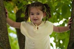 Een grappig vier-jaar-oud meisje met een vlechtkapsel en in een geel Stock Afbeelding
