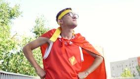 Een grappige gelukkige kerel in superherokostuum doet sporten in p stock video