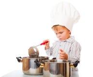 Een grappige jongen beeldt een kok af Stock Foto