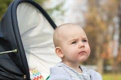 Een grappige kleine babyjongen in a in een kinderwagen Stock Foto