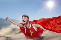 Een grappige super heldenvlieg boven de wolken in de hemel Stock Foto