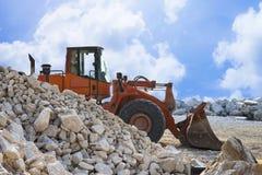 Een graver bouwt een dam van witte stenen op een bouwwerf - beeld op witte achtergrond voor gemakkelijke selectie royalty-vrije stock fotografie