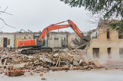 Een graver die huizen voor wederopbouw vernietigen Royalty-vrije Stock Foto