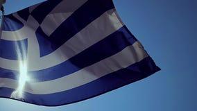Een Griekse vlag die in de wind met een blauwe hemel golven stock videobeelden