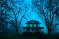 Een griezelig huis op een mistige dag stock foto