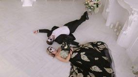 Een griezelig paar met make-up voor Halloween ligt op de vloer in Carnaval-kostuums stock videobeelden