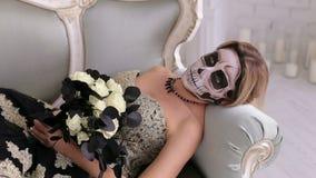 Een griezelige vrouw met make-up in de vorm van een schedel ligt op een retro bank Halloween stock footage