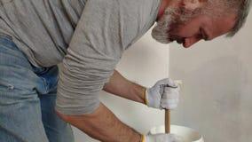 Een grijs-haired gebaarde mens mengt witte verf in een emmer door een stok en giet in de container stock video