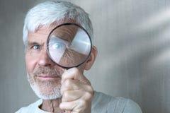 Een grijs-haired mens die in lichte kleren door een vergrootglas kijken royalty-vrije stock foto's