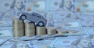 Een grijs model van een auto met muntstukken in de vorm van een histogram op een dollarsachtergrond Concept het lenen, besparinge Stock Foto's