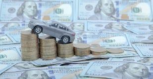 Een grijs model van een auto met muntstukken in de vorm van een histogram op een dollarsachtergrond Concept het lenen, besparinge Stock Afbeelding
