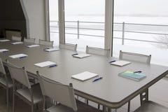 Een grijze lijst met het grijze stoelen en notitieboekjes leggen Stock Afbeelding