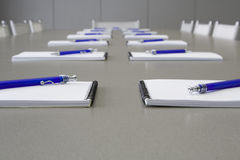 Een grijze lijst met het grijze stoelen en notitieboekjes leggen Royalty-vrije Stock Afbeelding