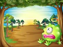 Een groen monster bij het bos die onder de boom rusten Stock Afbeeldingen