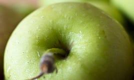 Een groene appel in dalingen van water Het macro ontspruiten Selectieve nadruk stock fotografie