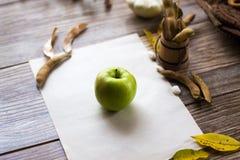 Een groene appel op een wit blad op een houten achtergrond Royalty-vrije Stock Foto's
