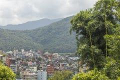 Een groene bergvallei onder de regenhemel met grijze wolken en de stad op de achtergrond van verse bamboestruik stock foto's