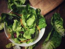 Een groene groente in een kom groene salade op de houten lijst Stock Foto