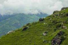 Een groene helling met rotsen en wolken stock afbeelding