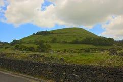 Een groene heuvel in de landbouwgronden van de Azoren Stock Foto