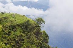 Een groene heuvelige klip met bewolkte hemel stock afbeeldingen