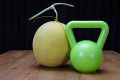 een groene kettlebell en een meloen stock afbeelding