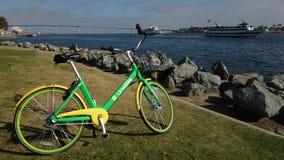 Een groene Limebike wordt geparkeerd bij San Diego Bay stock fotografie