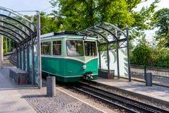 Een groene tandradbaanauto die zich op de sporen bij de bushalte bevinden stock afbeeldingen
